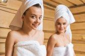 atraktivní mladé ženy s ručníky relxing v sauně a při pohledu na fotoaparát