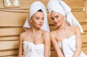 krásné mladé ženy s ručníky relxing v sauně a při pohledu na fotoaparát