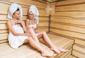schöne junge Frauen sitzen auf Bank in der Sauna