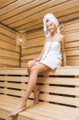 Fotografie atraktivní mladá žena sedí v sauně s ručníkem