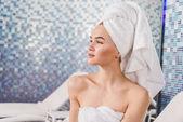 Fotografie promyšlené atraktivní žena s ručníkem na hlavě v lázních