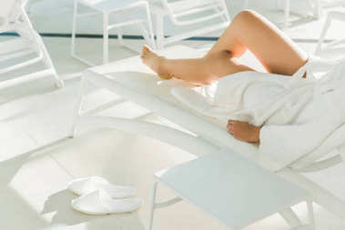 cropped shot of woman in bathrobe relaxing at spa