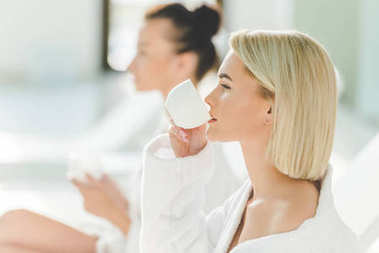 beautiful young women drinking coffee at spa center