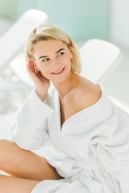 beautiful young woman in bathrobe relaxing with naked shoulder sitting on sofa at spa