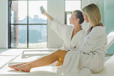 attractive young women using smartphone together at spa center