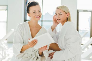 beautiful young women using tablet at spa center