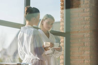 beautiful young women in bathrobes drinking coffee