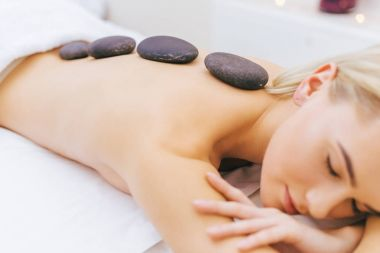 close-up shot of young woman getting stone therapy at spa salon