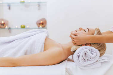 attractive young woman getting facial massage at spa salon