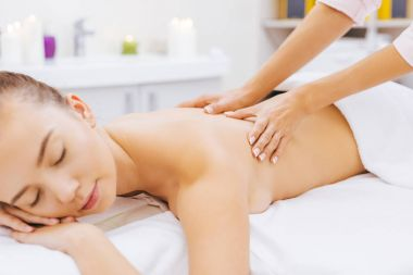 relaxed young woman having massage at spa