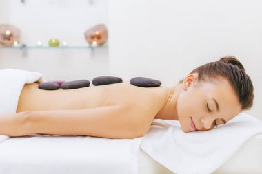 beautiful young woman having stone therapy at spa salon