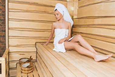 beautiful young woman relaxing on bench at sauna