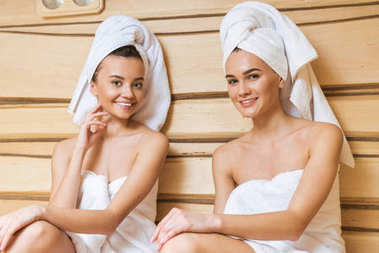 beautiful young women relaxing in sauna and looking at camera