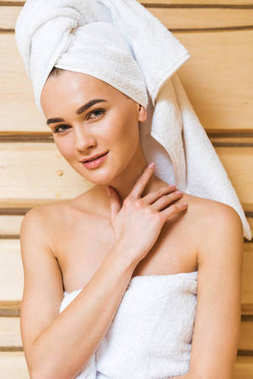 beautiful young woman covered with towel touching her perfect skin at sauna