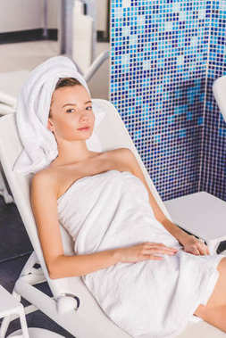 beautiful young woman relaxing on sunbed at spa salon