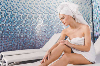 beautiful young woman covered with towel touching her leg at spa