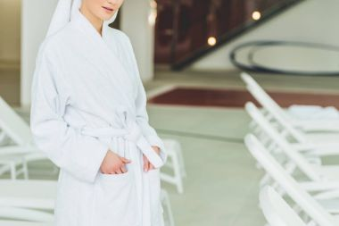 cropped shot of young woman in bathrobe at spa salon