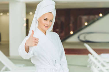 smiling young woman in bathrobe at spa salon showing thumb up