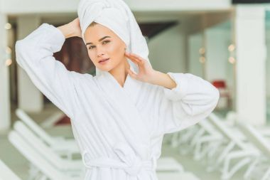 attractive young woman in bathrobe and towel on head at spa salon