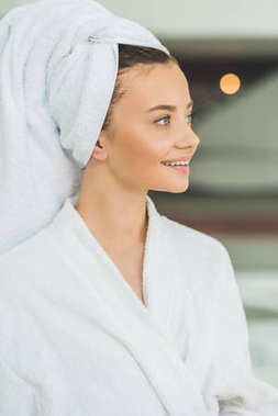 smiling young woman in bathrobe and towel on head at spa salon