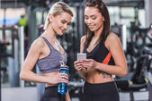Photo happy sportive women checking training results on smartphone at gym