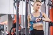 Fotografie junge Frau Prüfung Fitness-Tracker nach dem Training im Fitness-Studio