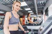Fotografie attraktive sportliche Frau, die auf Laufband im Fitnessstudio mit Kopfhörer