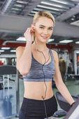 Fotografie attraktive junge Frau Musik hören mit Kopfhörern in Turnhalle