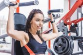 young attractive woman working out with gym machine