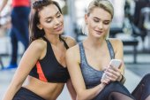 mladý sportovní ženy, které užívají smartphone v tělocvičně