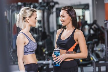 happy athletic women in modern sportswear talking to each other at gym