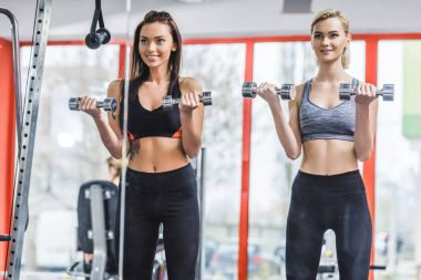 mirror reflection of sportive women working out with dumbbells at gym