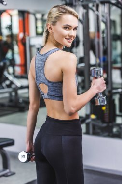 cropped shot of young woman working out with dumbbells at gym