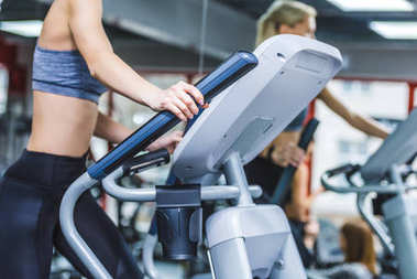 cropped shot of sportive woman working out on elliptical machine at gym