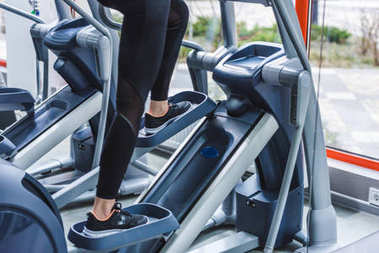 cropped shot of woman working out on elliptical machine at gym
