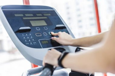 cropped shot of woman setting up elliptical machine at gym