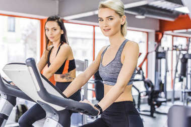smiling athletic women working out on elliptical machines at gym