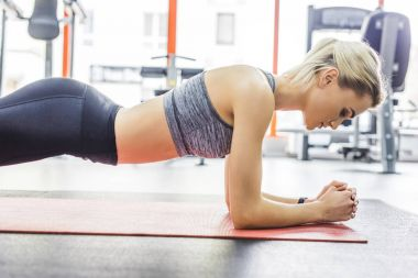 young sportive woman doing plank exercise on yoga mat at gym
