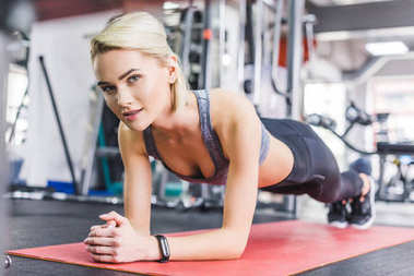young beautiful woman doing plank exercise on yoga mat at gym