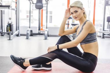 young sportive woman relaxing on yoga mat at gym after working out