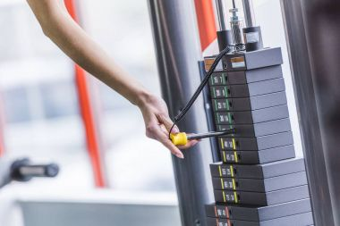 cropped shot of woman adding weight bars on gym machine
