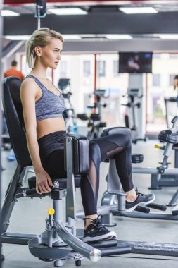 attractive young woman working out on gym machine