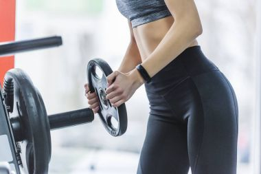 cropped shot of sportive woman adding weight plate to gym machine
