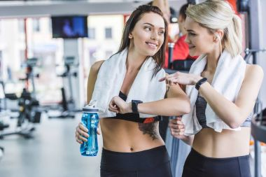 sportive women with towels checking fitnes results with smart watch after training at gym