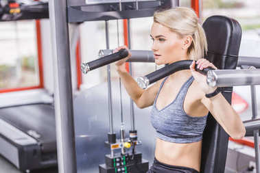 young beautiful woman working out with gym machine