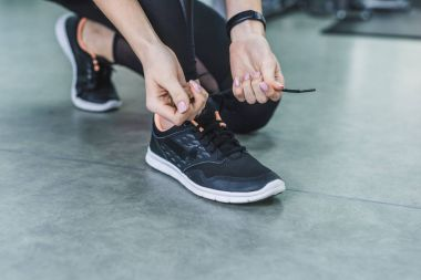 cropped shot of woman lacing up sneakers before training