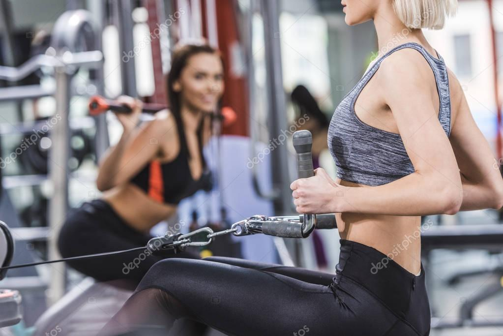 cropped shot of sportive women working out at gym