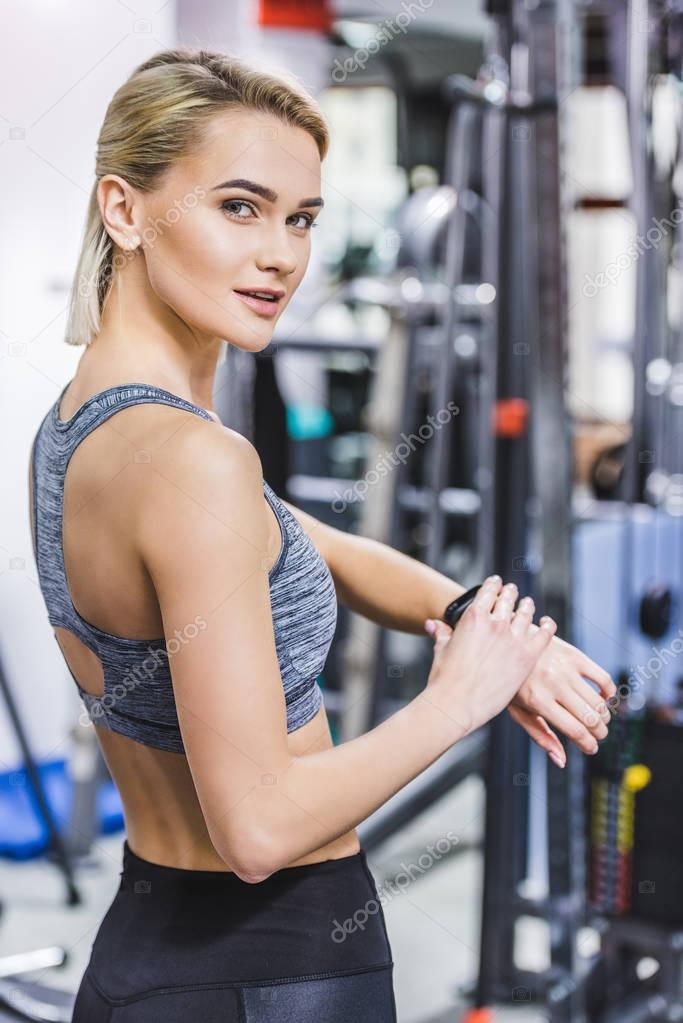 beautiful young woman checking fitness tracker after workout at gym