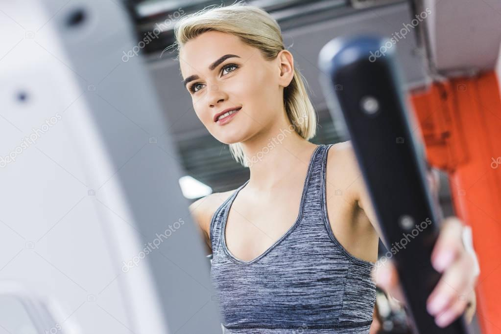 close-up shot of woman working out on elliptical machine at gym
