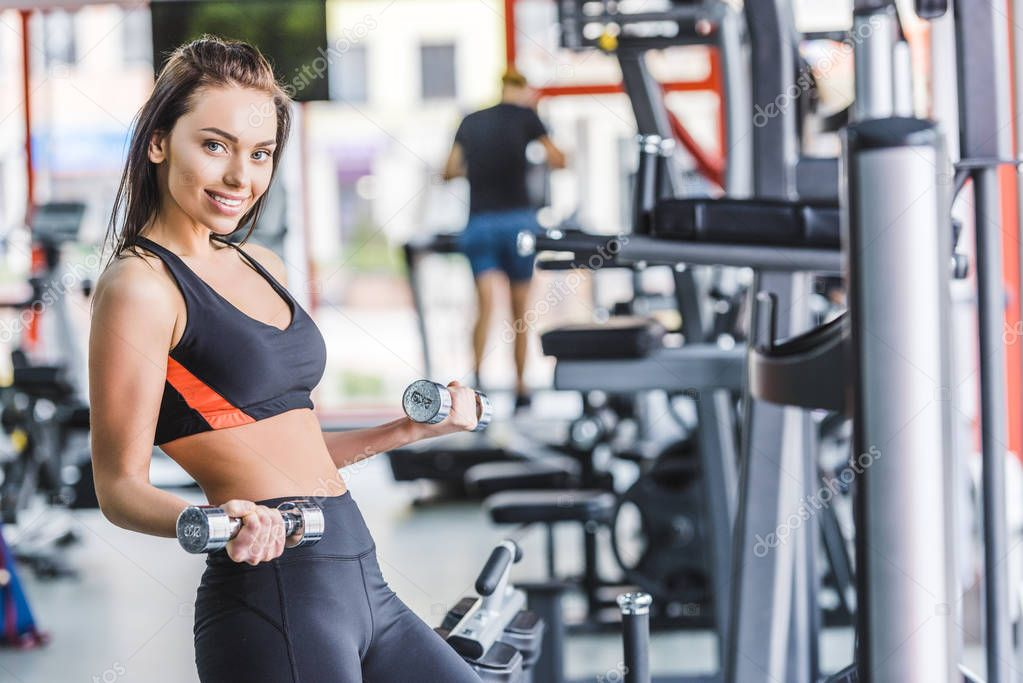 young sportive woman doing exercise with dumbbells at gym